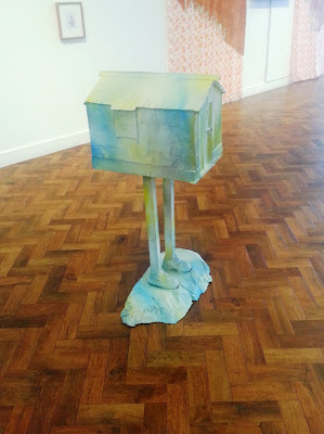 Ronnie van Hout's 'Cold shoulder to cry on' sculpture of a house on legs in a gallery.