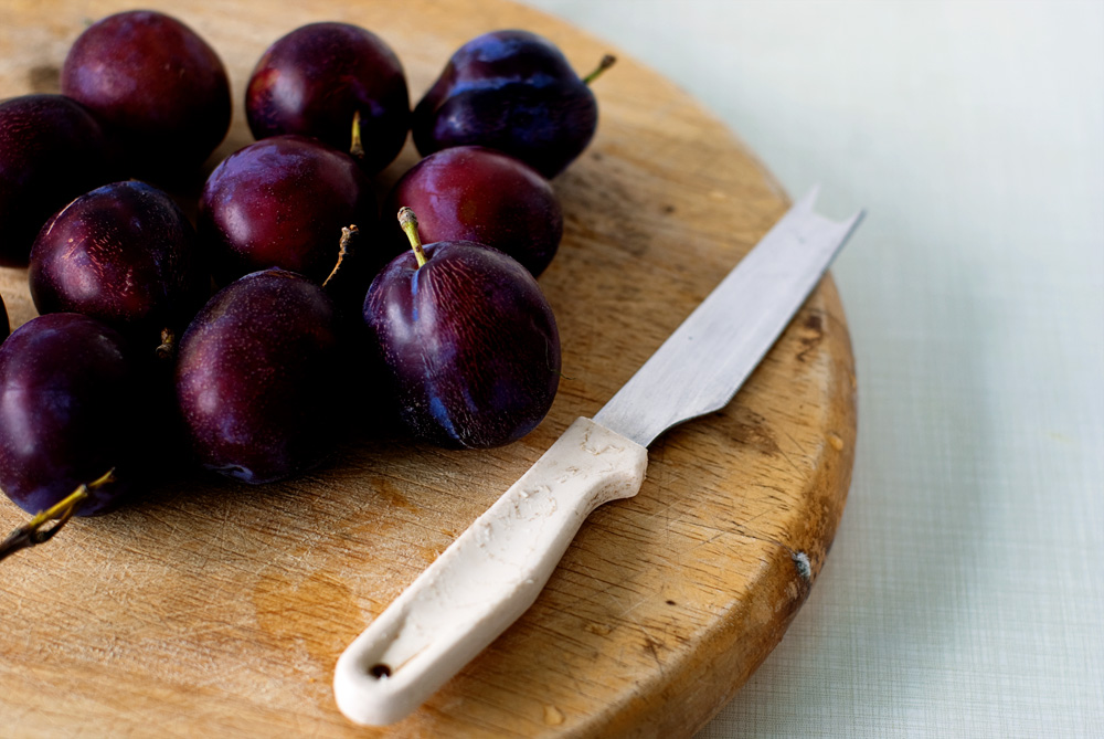 several plums on a cutting board with a knife adjacent
