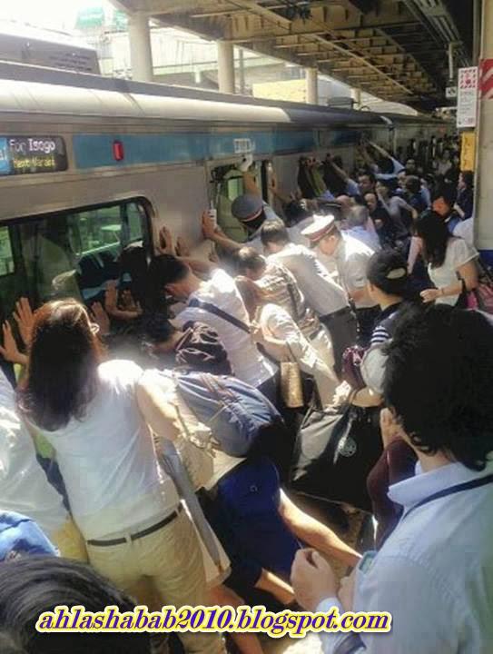 بالصور-كيف تضافر اليابانيون لإنقاذ إمرأة قبل دهسها تحت قضبان القطر