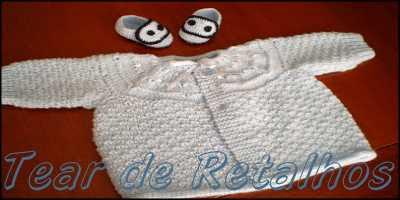 Casaquinho de bebê azul em tricô, com seu lindo par de sapatinhos.