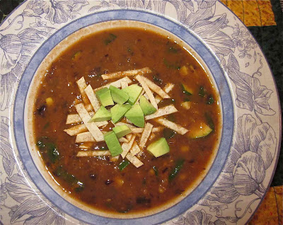 spicy tortilla soup with fresh greens and avocado