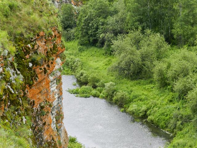 Отвесная рыжеватая скала на фоне реки Багаряк