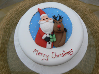 Merry Christmas cake decoration with Smiling Santa Claus giving X mas gifts to reindeer image free download religious wallpapers and desktop background pictures