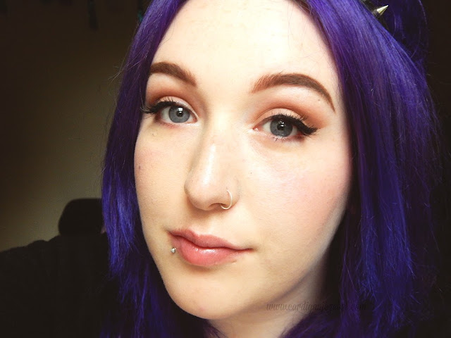 Girl with purple hair and blue eyes poses for makeup of the day photo with winged eyeliner