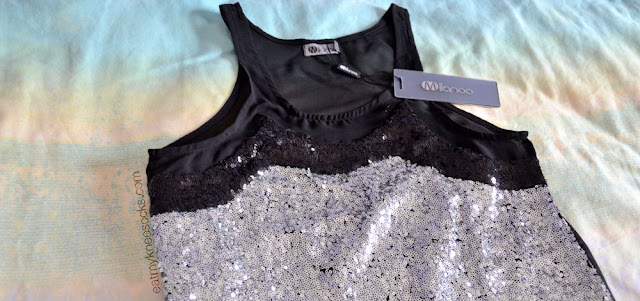 This unique, festive sleeveless top features silver and black sequins combined with sleek mesh paneling.