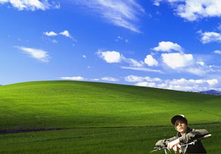 Justin Bieber free posters wallpapers riding his a bike and watching the fans in classic Bliss Landscape background