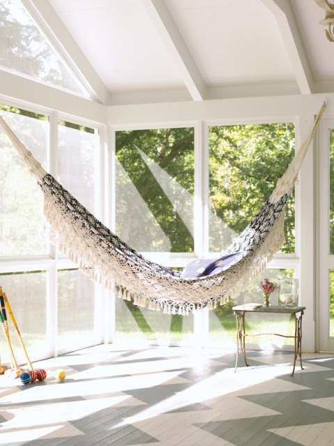 Sun room with floor to ceiling glass windows, Chevron pattern painted on the wood floor and an indoor Lovely hammock