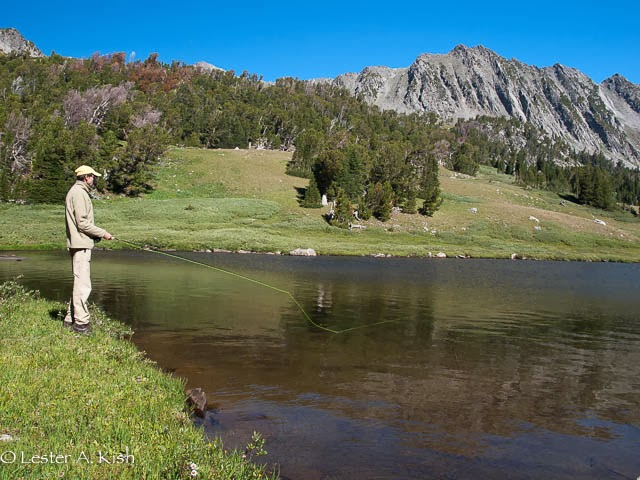 Angler fishes for cutthroat trout, Thompson Lake, Spanish Peaks, Montana.