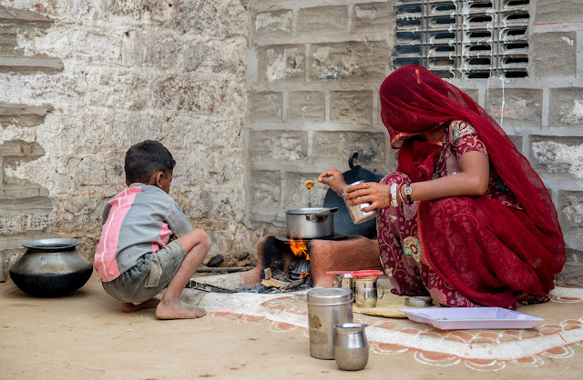 A mother and her young boy child making tea in a small pot over a fire outside their hut in Rajasthan, India