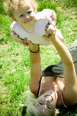 Mamá jugando con su hijo en el césped. Mamá feliz con su hijo.