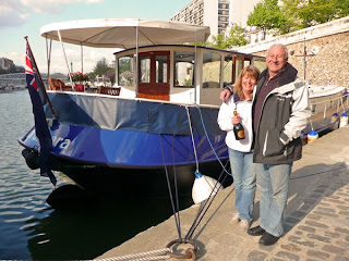 Jane and Mike standing in front of their barge.  Jane is holding a bottle of Champagne and Mike has his arm around her.