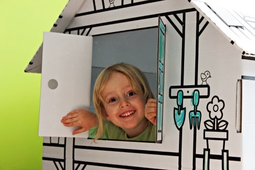 child peeking out the window of a play house