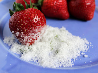 Front view of strawberry dipped in basil sugar, on blue plate.