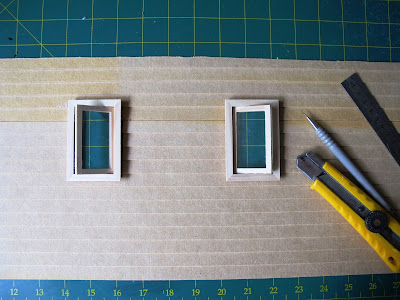 Wall of a dolls' house miniature kit, with window holes cut and windows installed.