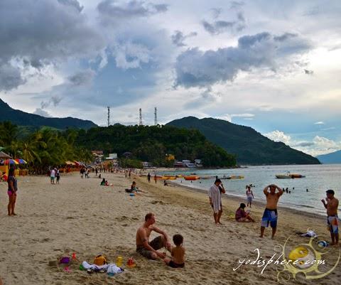 Tourists enjoying the white beach at Puerto Galera, Oriental Mindoro Philippines