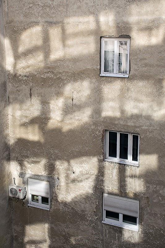 Prozori na zgradi kao samvoljno izbušene rupe i odraz sa drugog objekta