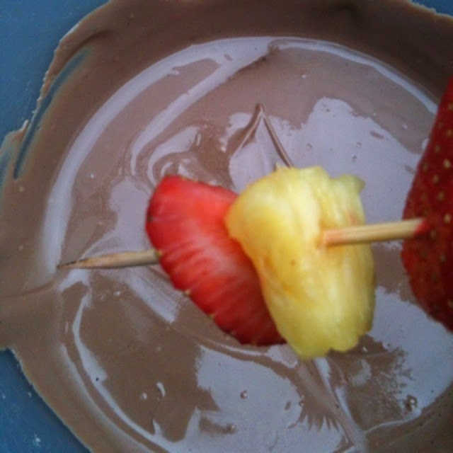 pineapple and strawberry kebabs dipped into melted chocolate