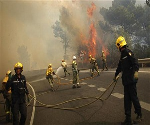 Firefighters controlling wildfire on the road between Marbella and Monda in Ojen, Southern Spain