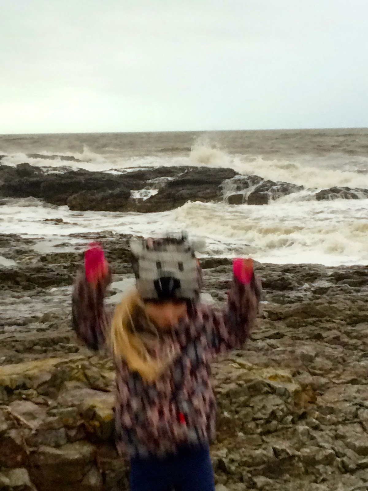 child jumping off rocks Welsh  coast