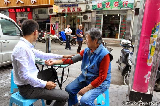 A doctor takes a patient's blood pressure at his streetside clinic photograph