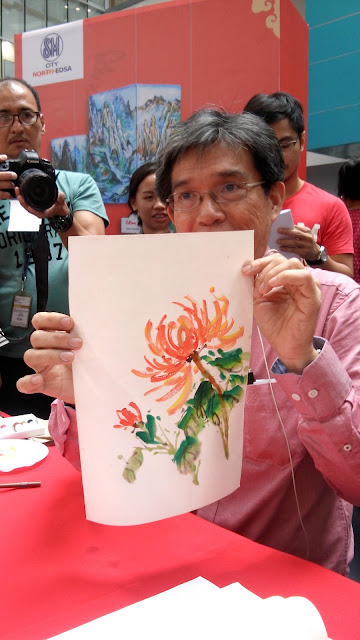 Bamboo, chrysanthemum and landscape were painted swiftly by Dr. Alex Chan Lim's experienced hands.