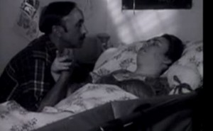A thin, middle-aged white man sits at the bedside of a disabled young woman, looking into her face and holding her hand