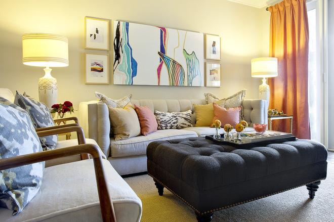 Decoração de sala pequena em tons neutros com sofá de três lugares e poltronas. Um puf faz a vez de mesa de centro.
