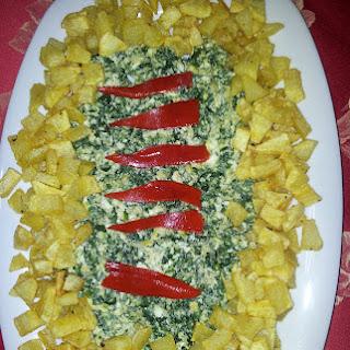 Huevos rotos con espinacas y patatas fritas