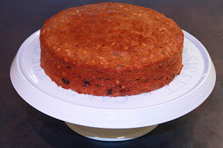 Carrot cake on a stand, before decorating with cream cheese frosting and caramelised nuts