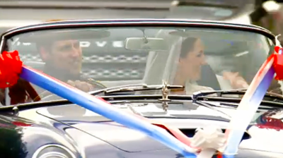 A close up of the Duke and Duchess of Cambridge driving off Buckingham Palace. YouTube 2011.