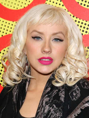 With short, airy bangs, Christina Aguilera's side-parted hairstyle is smooth on top and gradually phases into large ringlet curls.