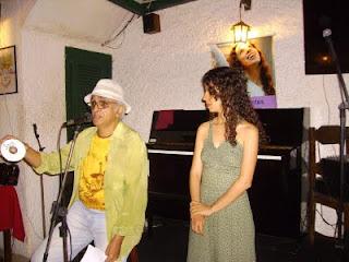 Na foto, Marcondes Mesqueu fala ao microfone, com um cd nas mãos escrito Sara, e a própria ao seu lado.