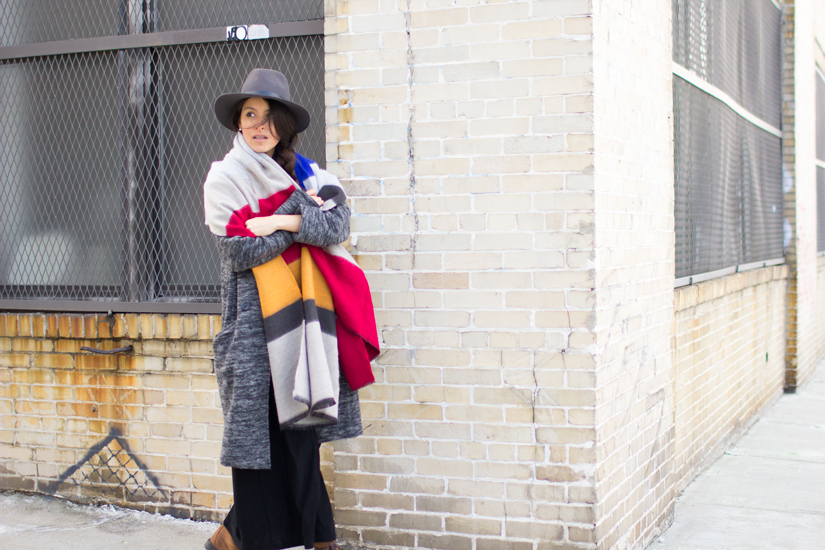 Maria Copello style and fashion blogger at notesofstyle.com is wearing a long grey coat, black vintage dress, zara scarf, rag and bone hat, vintage boots, and Madewell black leather bag in Bushwick Brooklyn.