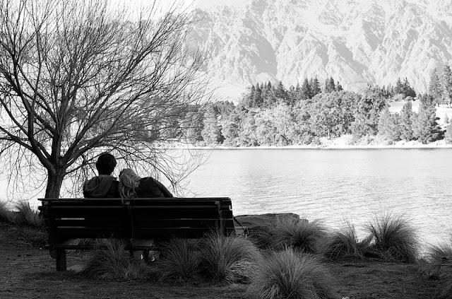 Paisaje en blanco y negro con pareja sentada en un banco