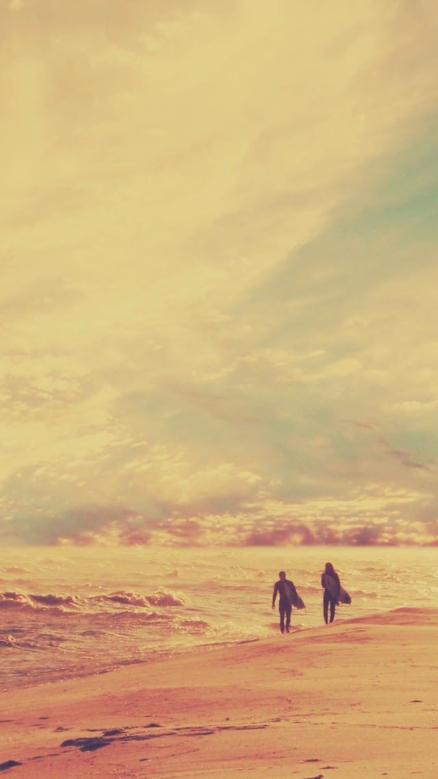 surfers walking on the beach sunset wallpapers for your mobile