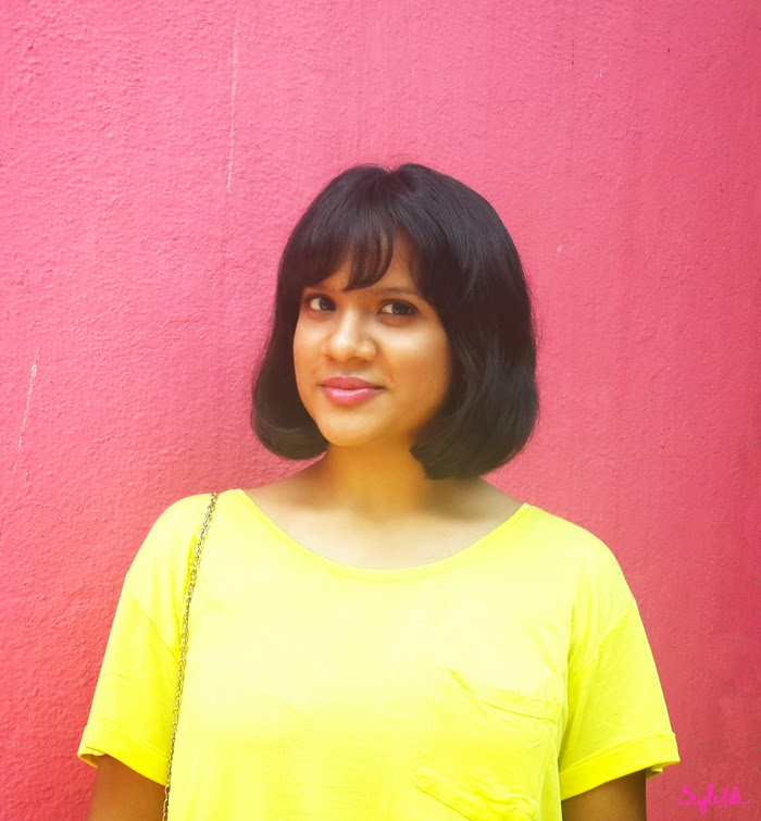 Dayle Pereira of Style File India wears a yellow shirt with pink lips on a pink background and sports a celebrity trending short bob hairstyle for the summer season