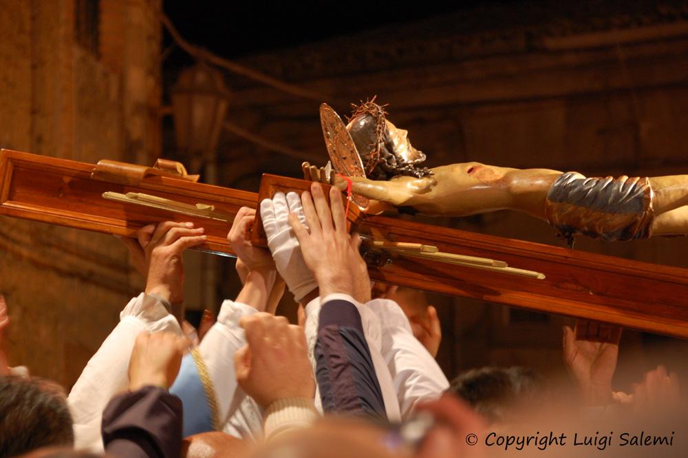 Le mani dei confrati accolgono il Crocifisso