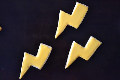 Lightning shaped sugar cookies on a black table.