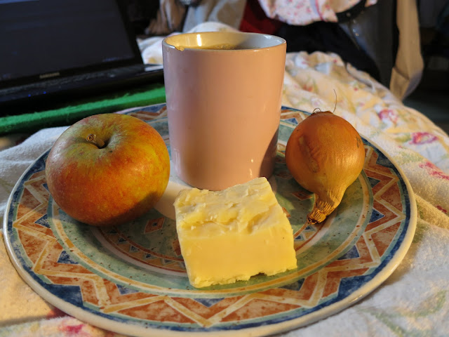 Apple, cheer, a cup of tead and an onion all on a plate.