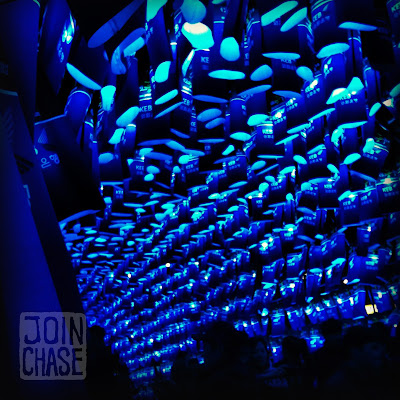 People walking under hundreds of blue lanterns in Seoul, South Korea.