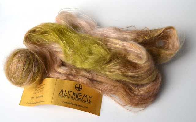 Silk mohair half in a ball and half a hank untwisted in light browns, fawns and muted greens.
