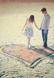 couple making heart of sand on beach