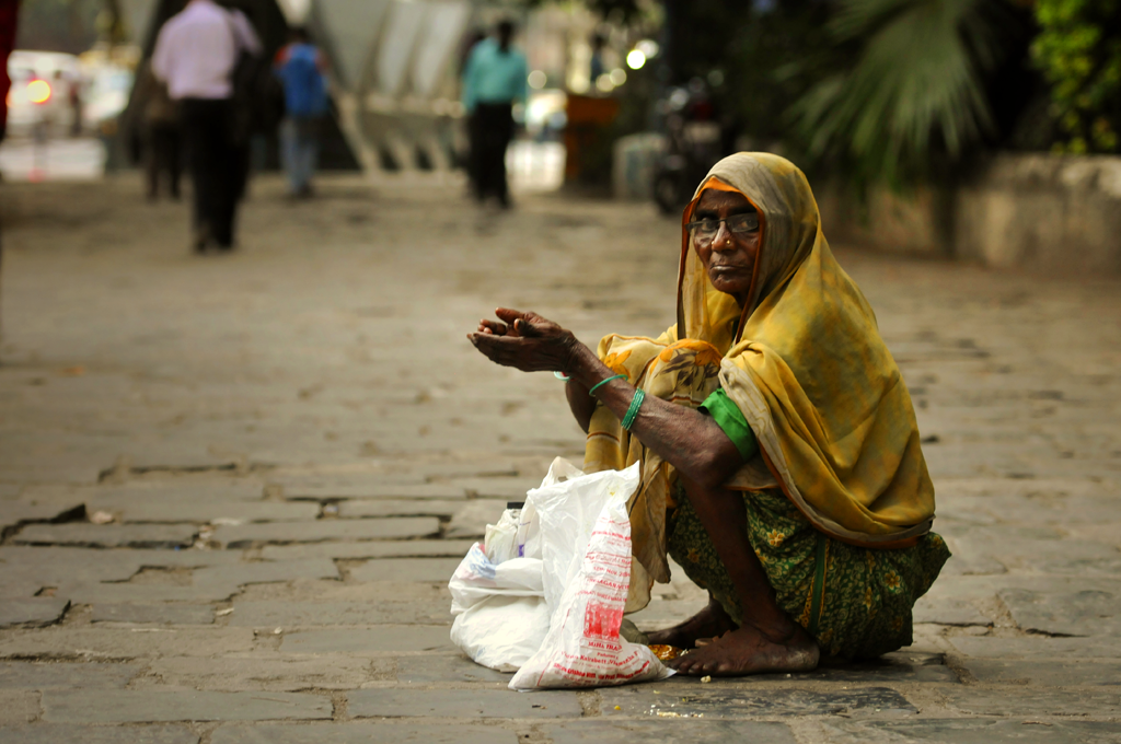 Bombay portraiture of a woman sitting on the ground begging.