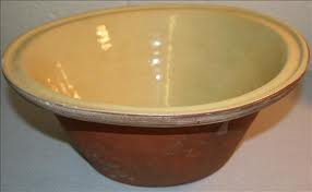 A large inverted cone shaped earthernware bowl, cream on the inside and chestnut brown on the outside.