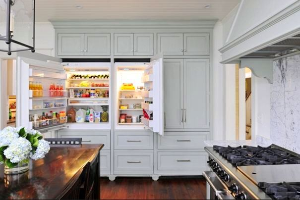 Alternative view of the kitchen and it's hidden fridge, grey cabinets, marble counter tops, casement windows, stained oak table dining room table surrounded by matching chairs and a chandelier