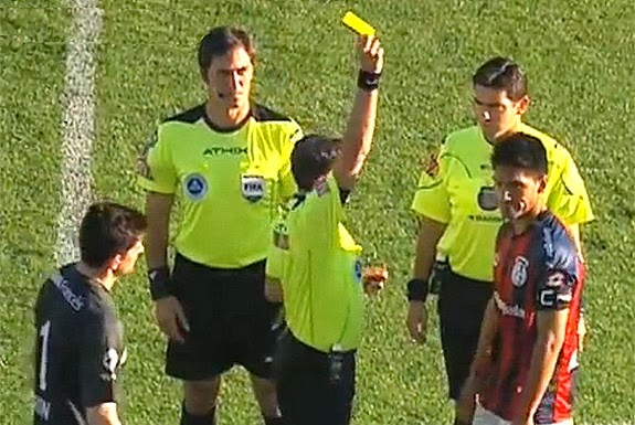 Referee shows the yellow card to San Lorenzo captain Pablo Alvarado before the game even started