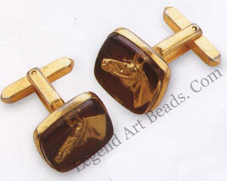 A pair of unsigned cufflinks in gold plated brass. The horse's head is reverse-cast into black glass and gilded to shine out from its background. Late 195os.