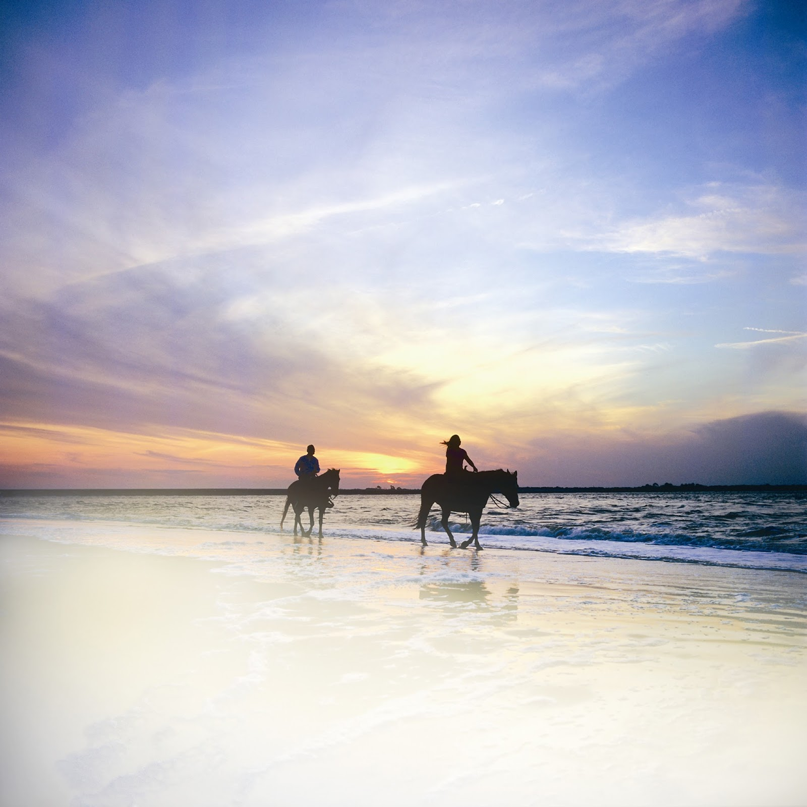 Horse back riding on the beach at sunset.