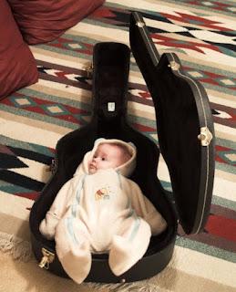 Gambar bayi lucu tidur di dalam gitar