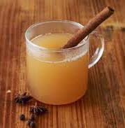 hot apple cider in a clear mug with a cinnamon stick sticking out of the cup and star anise sprinkled in front of the cup.
